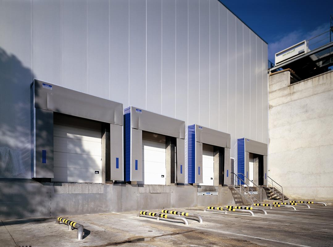 Molls de càrrega Els Molls de Carrega es composen de Portes Seccionals, Abrics Aïllants, Rampes, Taules o Plataformes Elevadores:  Abric aïllant de lames amb sistema autorretornable. La seva trama téxtil interior i el seu acabat en PVC lel fan resistent al fragament i al esquinçament. Les seves mides estandaritzades abarquen qualsevol tipus de camions.  Les Portes Seccionals s'adapten a qualsevol tipus de construcció. Els seus panells compactes aïllants i la garantía de seguretat en el seu funcionament i apertura ofereixen la màxima flexibilitat en la càrrega i descàrrega.  Rampa electro-hidràulica automàtica construïda amb la màxima elasticitat permesa per adaptarse a la caixa del camió. Equipada amb faldons anticizalla de recorregut telescòpic i bastidor autoportant reforçats.  Taula Elevadora hidràulica per a moll de càrrega y descàrrega, aconseguin qualquevol alçada del camió.