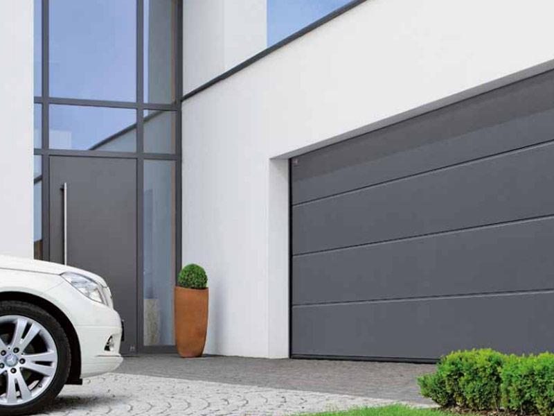 PORTES SECCIONALS La nostre porta seccional es una porta disenyada per aprofitar al màxim l'espai del seu garatge, ja que necessita un mínim espai per a la seva instal·lació. Està construïda amb panell sandwich de 40mm de gruix, inyectat amb alta densitat. Hi ha unes juntes de goma epdm en tot el perímetre de la porta per tal d'evitar l'entrada d'aire, aigua o petits elemets que puguin estar al carrer. Està construïda amb el marcatge CE de la comunitat europea. Hi ha diversos acabats de panells, acanalats, llisos rogosos... S'hi poden posar finestres, regilles de ventilació i altres accessoris. Tenim una gama àmplia de colors de la carta ral o bé imitació fusta. Es poden instal·lar amb automatisme o manuals amb pany i clau.  Contacti: portamatic@andorra.ad